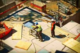 two contractors using tools and working on constructing a building
