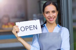 female business owner holding up and open sign