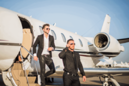 wealthy white males walking off of a private jet