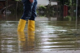 a person in yellow boots standing in flooded street