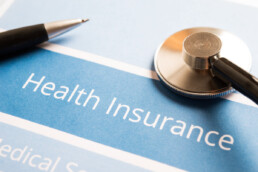 health insurance document with pen and stethoscope