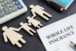 whole life insurance document next to paper cut outs of a family